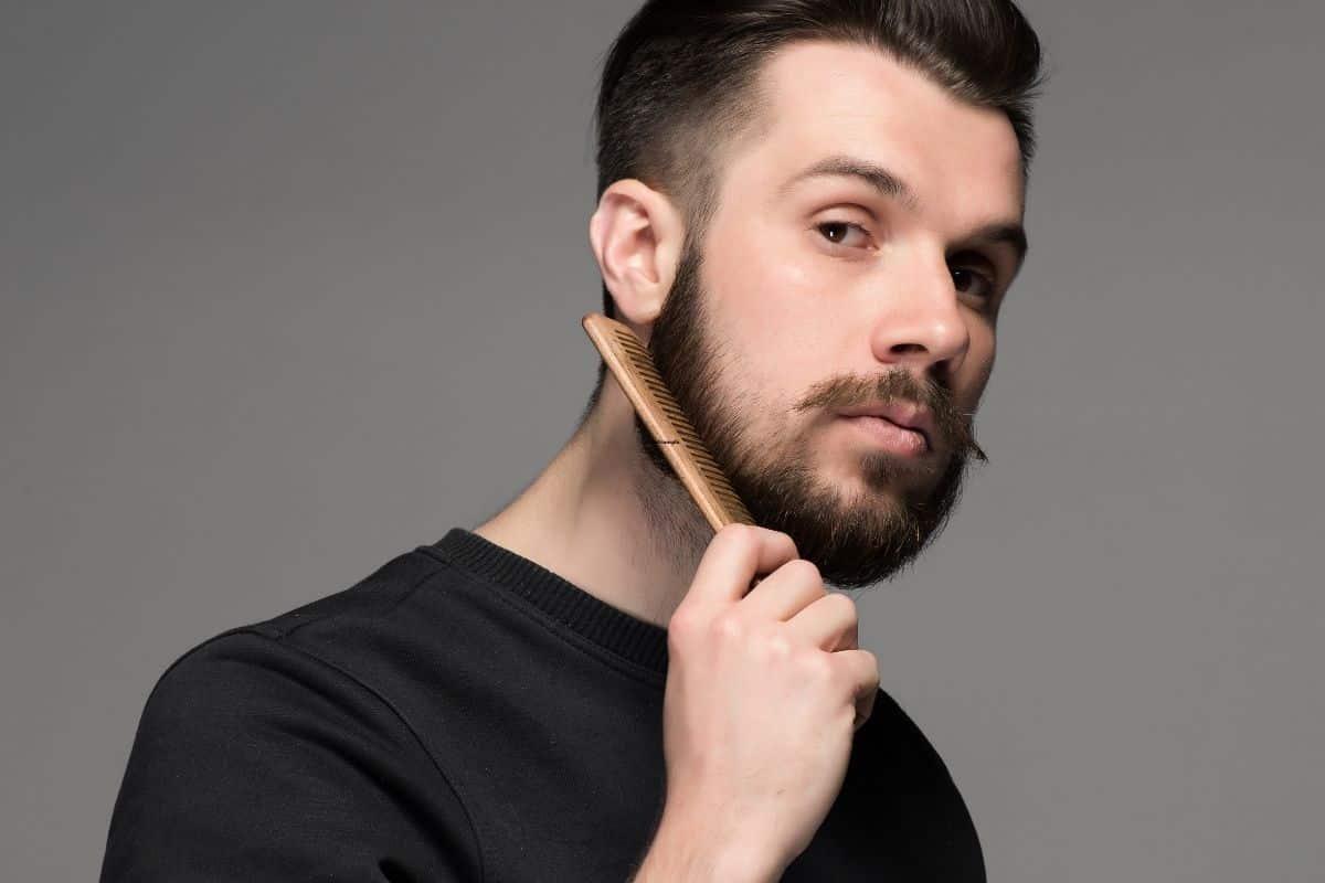 Mann pflegt Bart mit Bartkamm