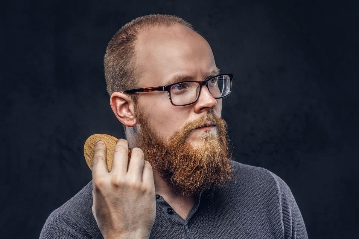 Mann kämmt sich seinen Bart mit einer Bartbürste